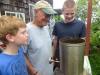 Jonah and Ezra helping Grandpa Bob roast