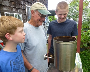 Jonah and Ezra helping Grandpa Bob roast